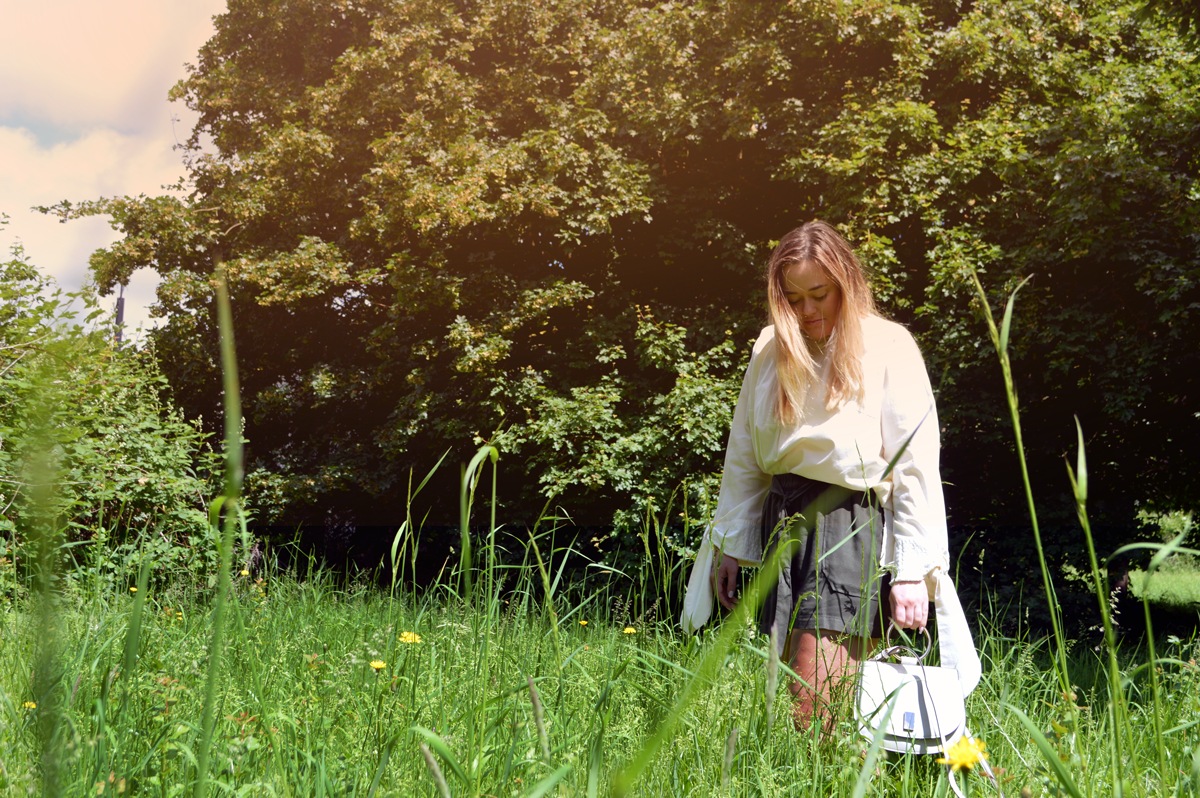 Hannah wearing Mango over-sized cream shirt with bows hanging down with khaki baggy shorts in a field on a sunny day.