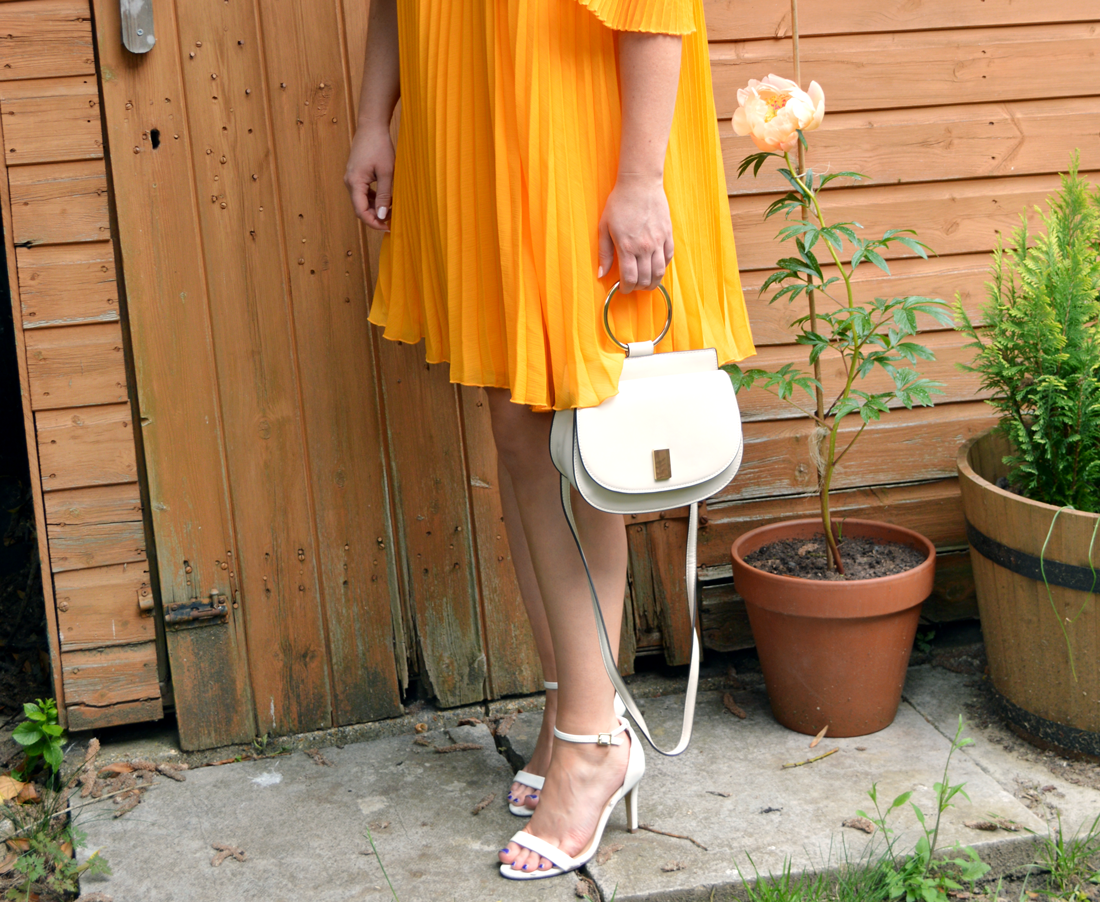 Hannah in a pleated and floaty yellow dress that comes just above the knee with barely there white heeled sandals with cream Mango bag with gold handle
