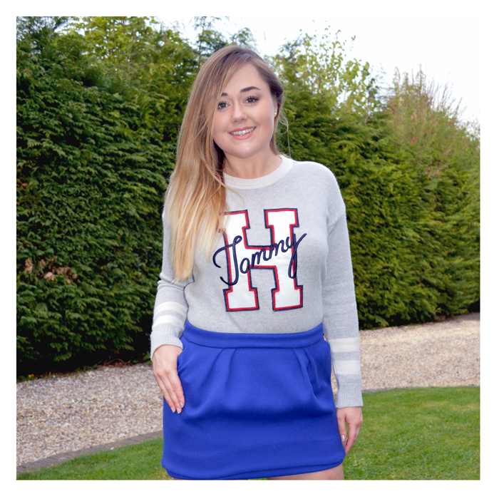 Hannah wearing a Tommy Hilfiger jumper with a bright blue skirt