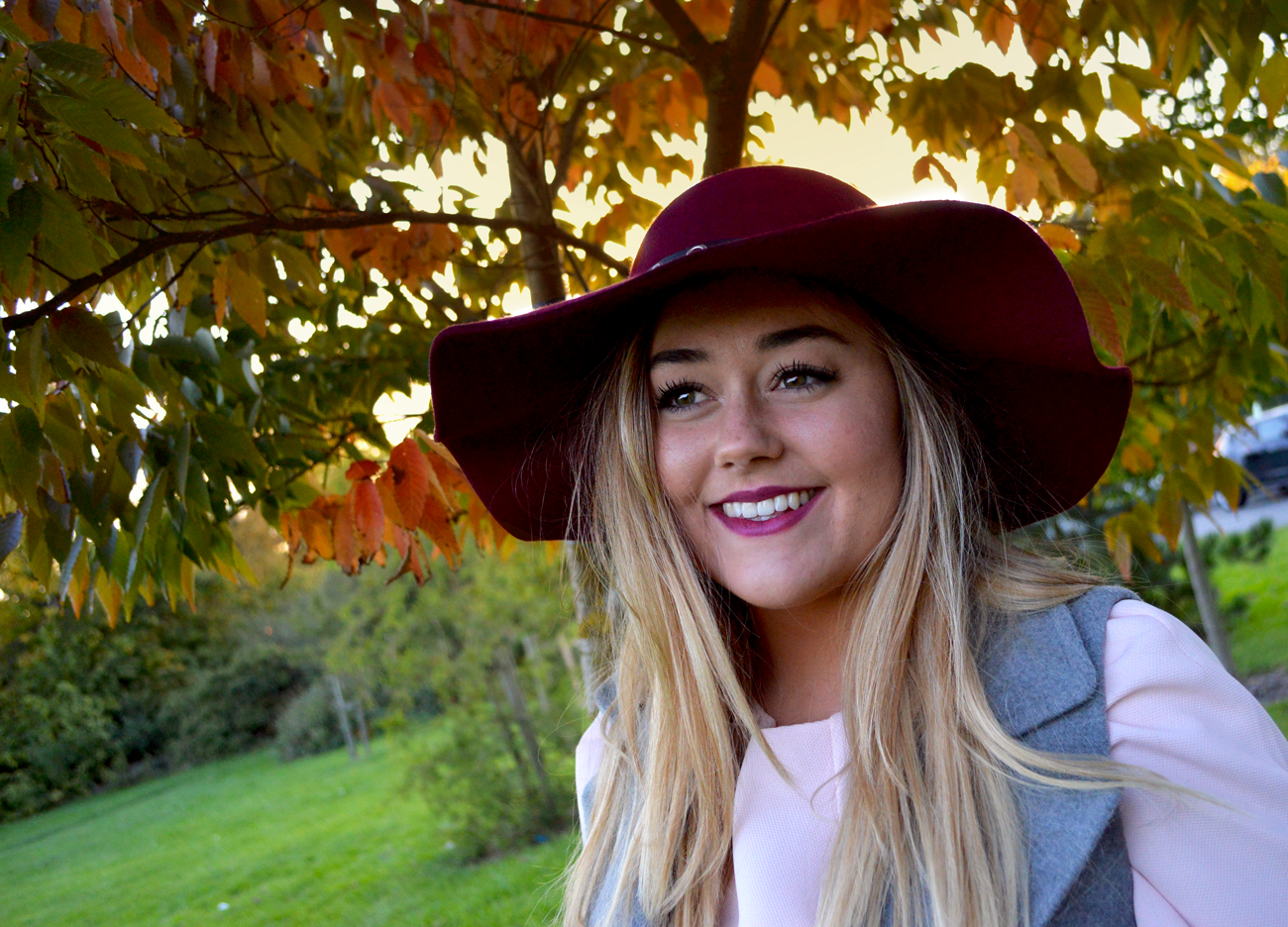 Close up shot of Hannah Gladwin with the sunset and autumn leave in the background. Wearing: Ted Baker dress and felt Burgundy floppy hat and Charlotte Tilbury 'Glastonberry' matte lipstick.