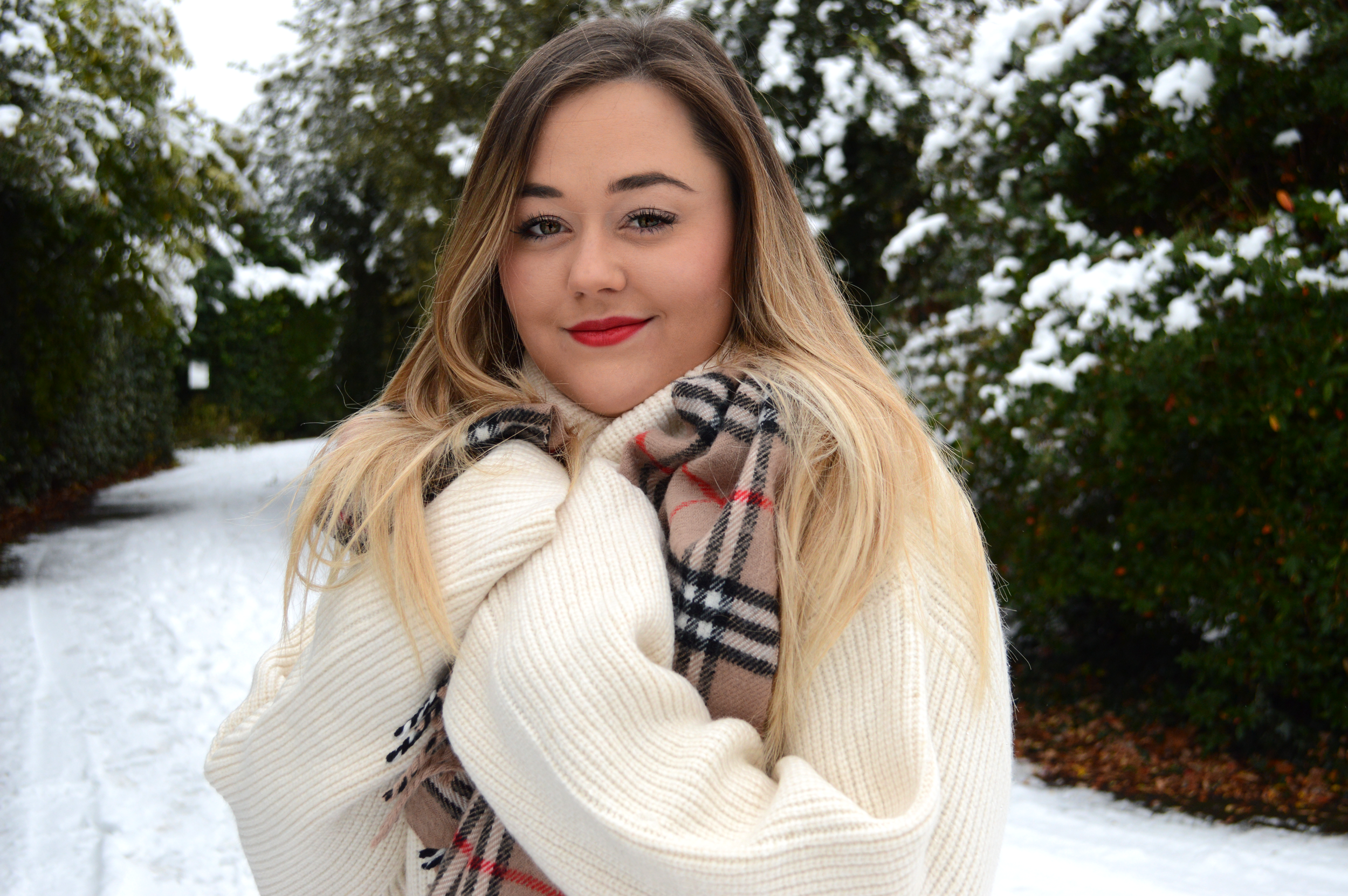 Why a red lip is more than just makeup | Red lipstick history. Hannah is in a cuddle H&M oversize jumper dress in cream, with classic Burberry check cashmere scarf. Wearing red lipstick in the snow.