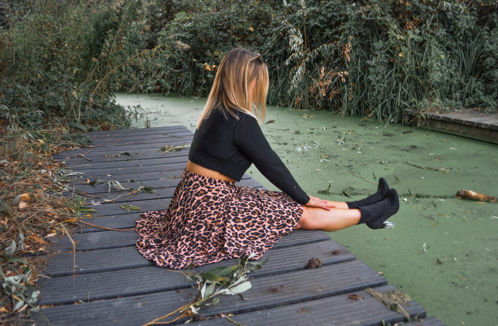 Hannah sitting by river wearing leopard print skirt and black turtleneck knit.