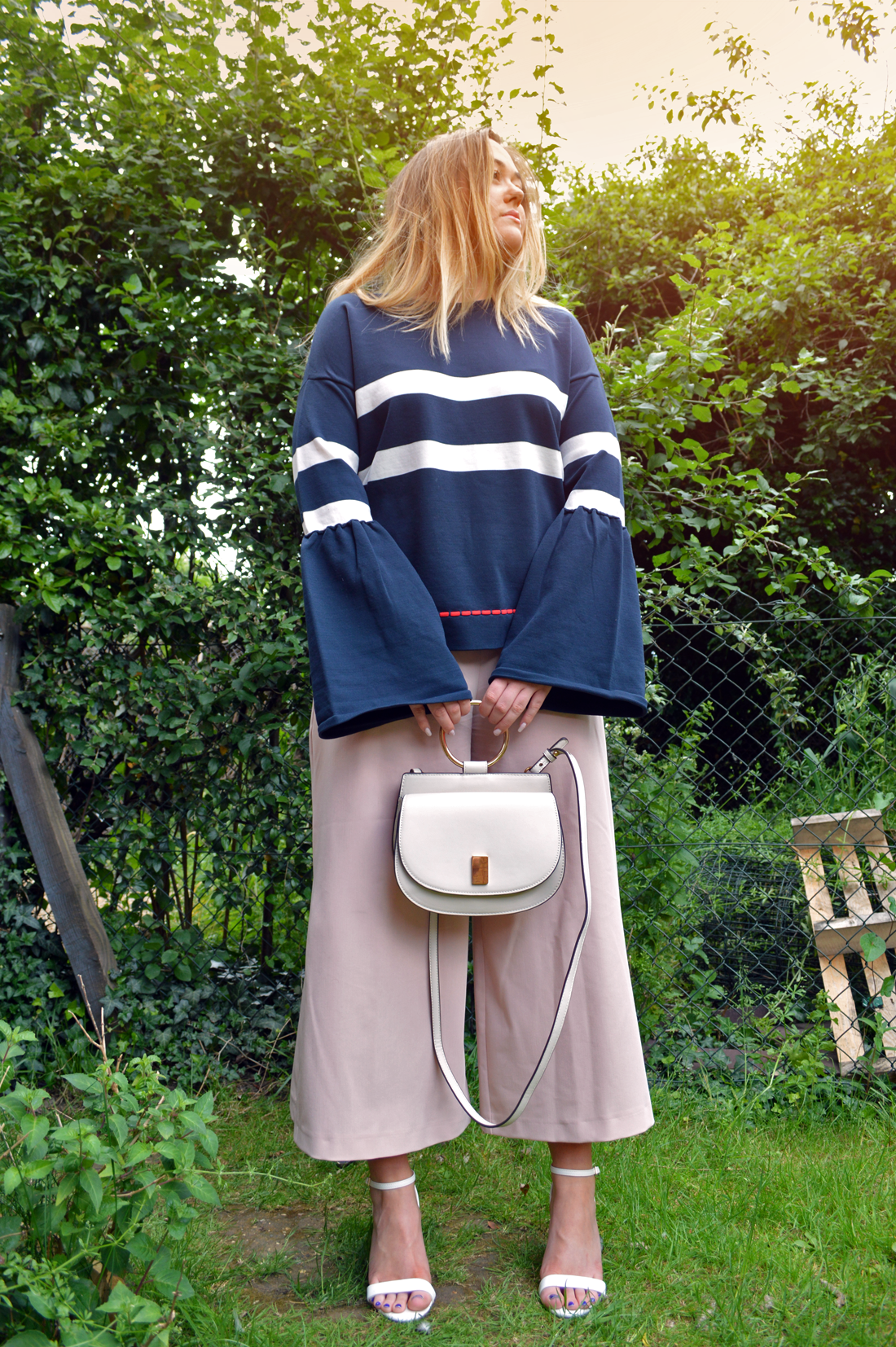 Hannah Gladwin wearing Asos nude culottes with side splits, with barely there white heeled sandals, with an over-sized navy knitted jumper with large sleeves, holding a cream Mango bag by its gold ring.