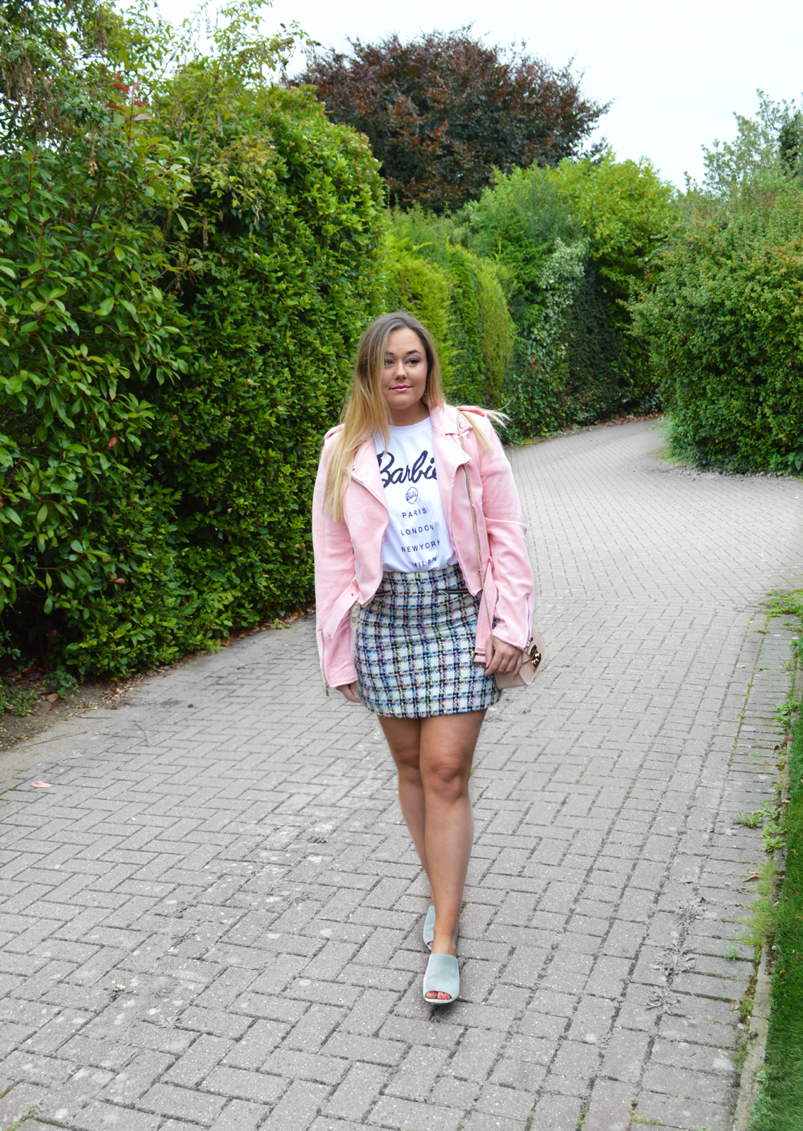 Hannah wearing Missguided x Barbie T Shirt with pink jacket and tweed skirt