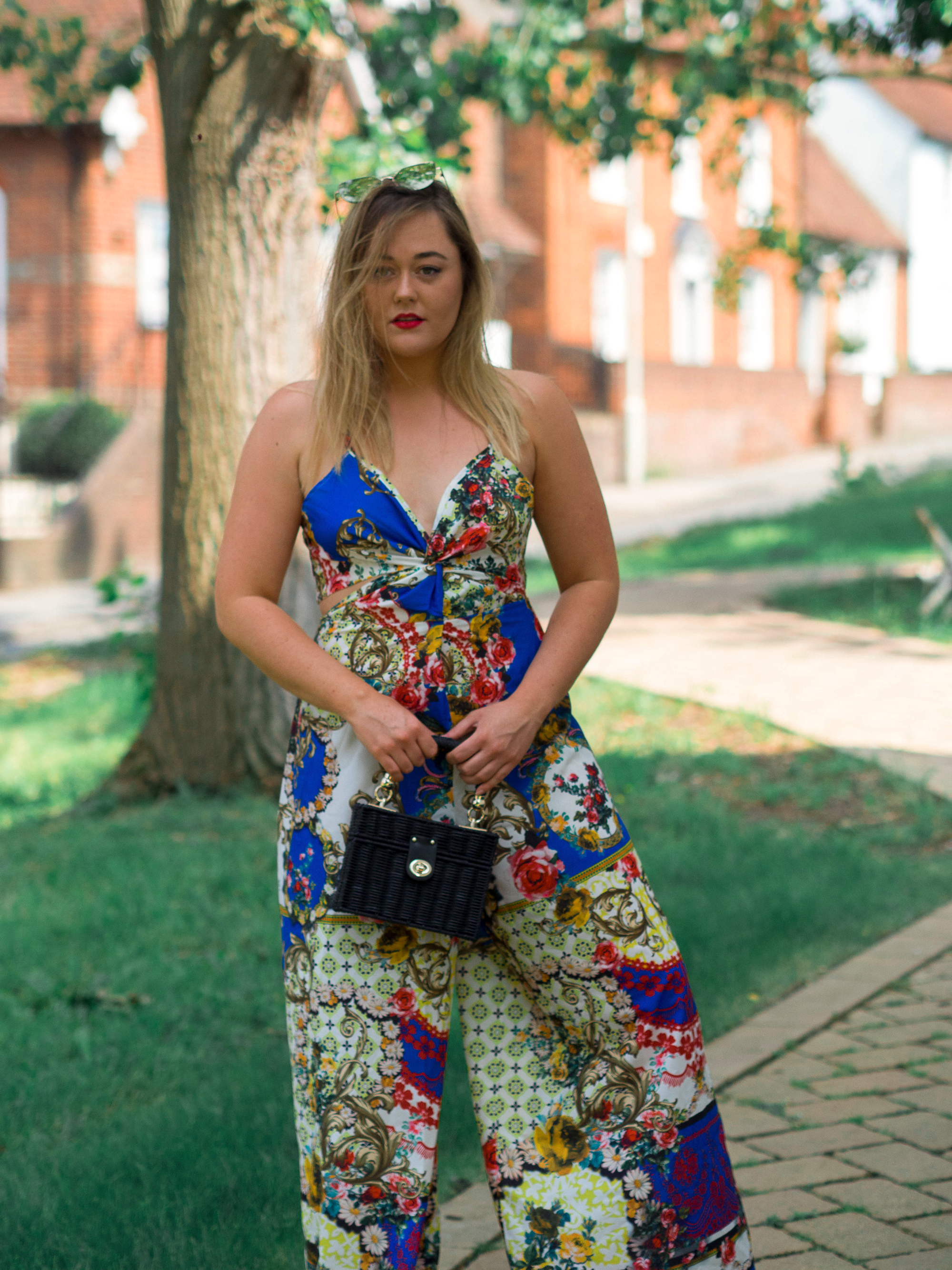 Hannah wears a scarf print jumpsuit in blue, red and gold baroque pattern. She holds a minaudiere box bag in black. Dolce & Gabbana designer inspired high-street look. Style inspiration. Fashion blogger. Photos taken by D Rayner photo