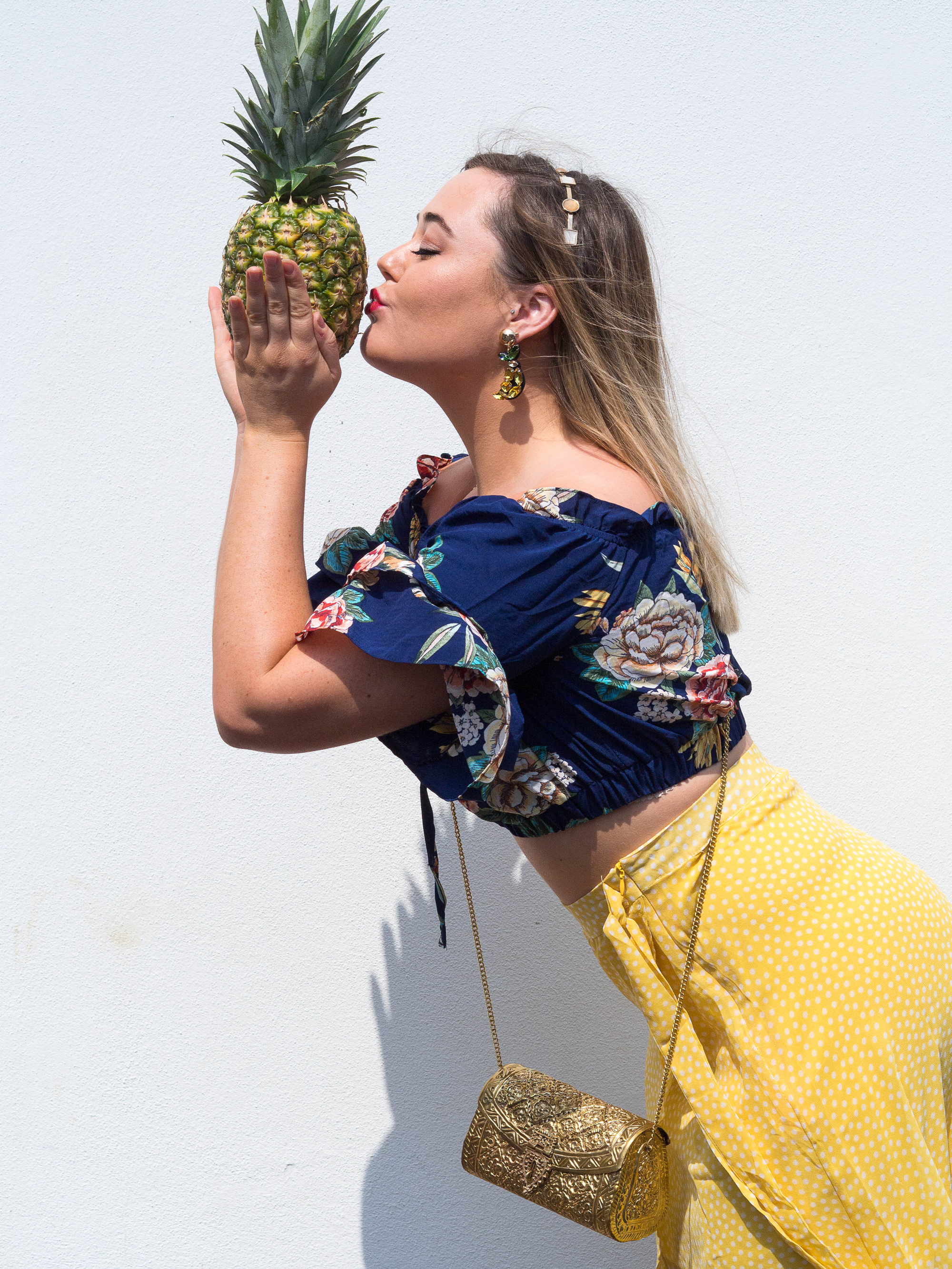 Hannah kisses a pineapple