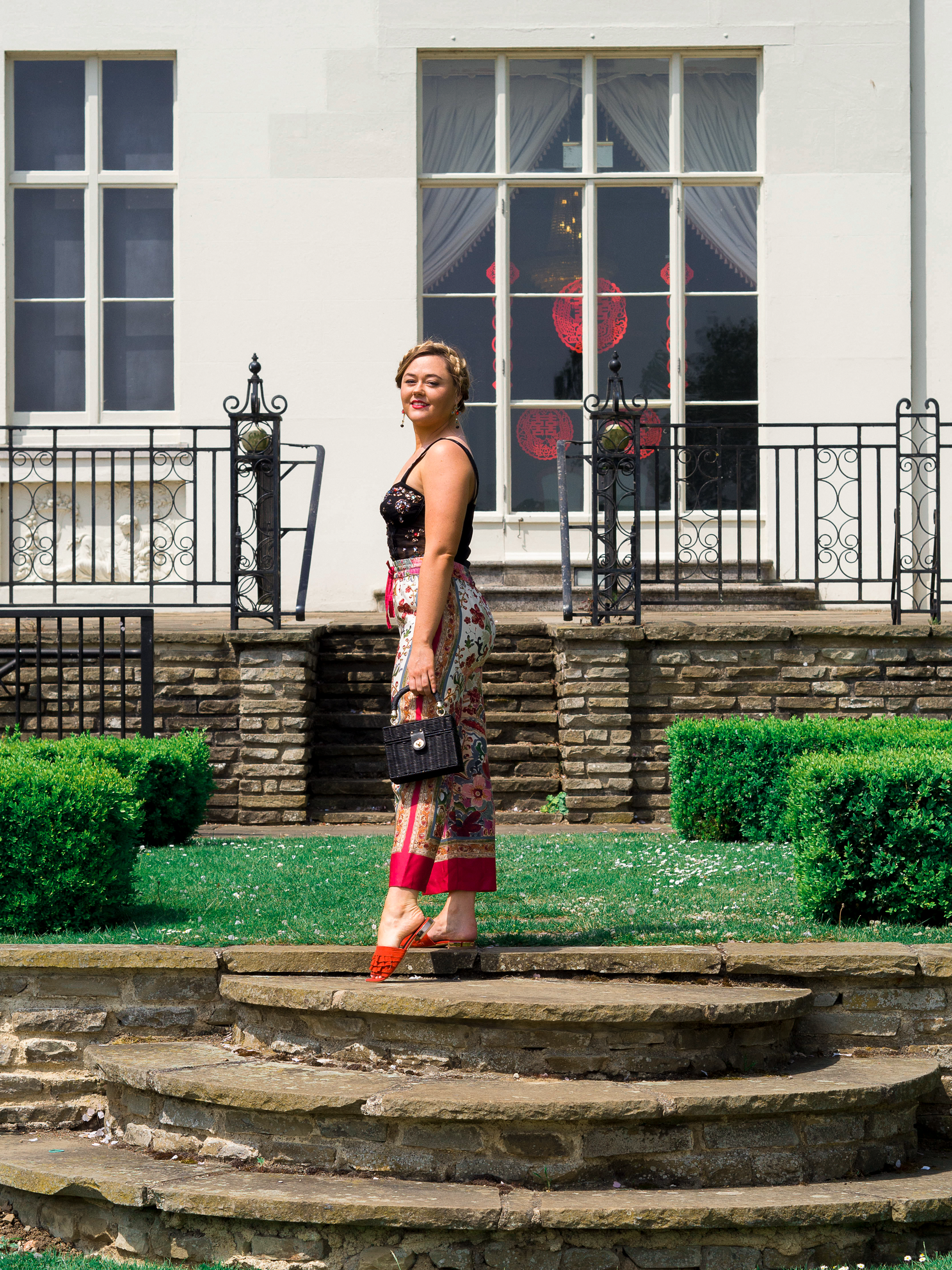 Hannah wears an embellished and jewelled black bustier with straps and baroque patterned red silky pyjama style trousers/pants. Shoes are red mules and she holds a black weaved wicker box bag outside a old white Manor House.