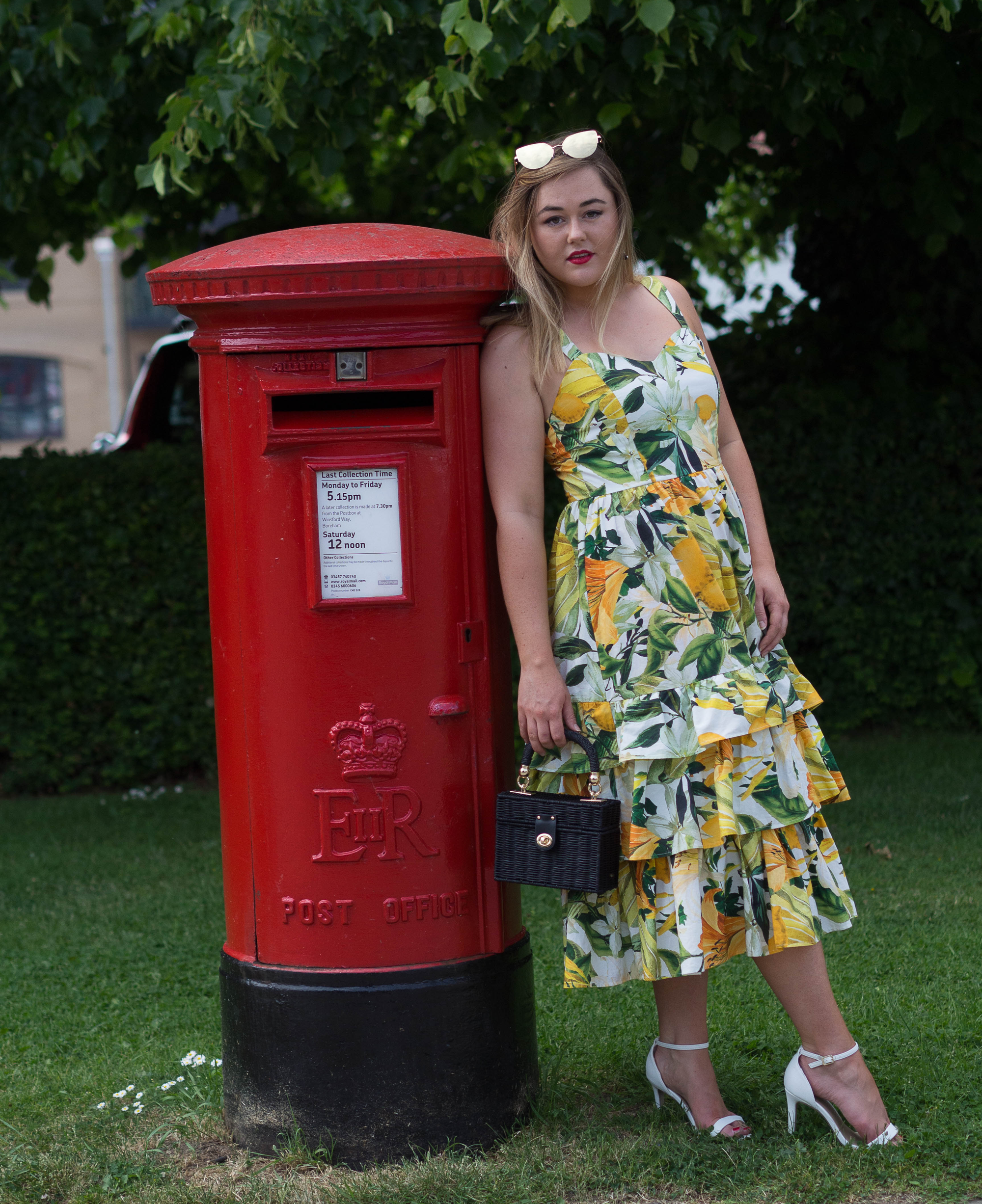 Hannah in yellow floral dress leaning on a red post box.