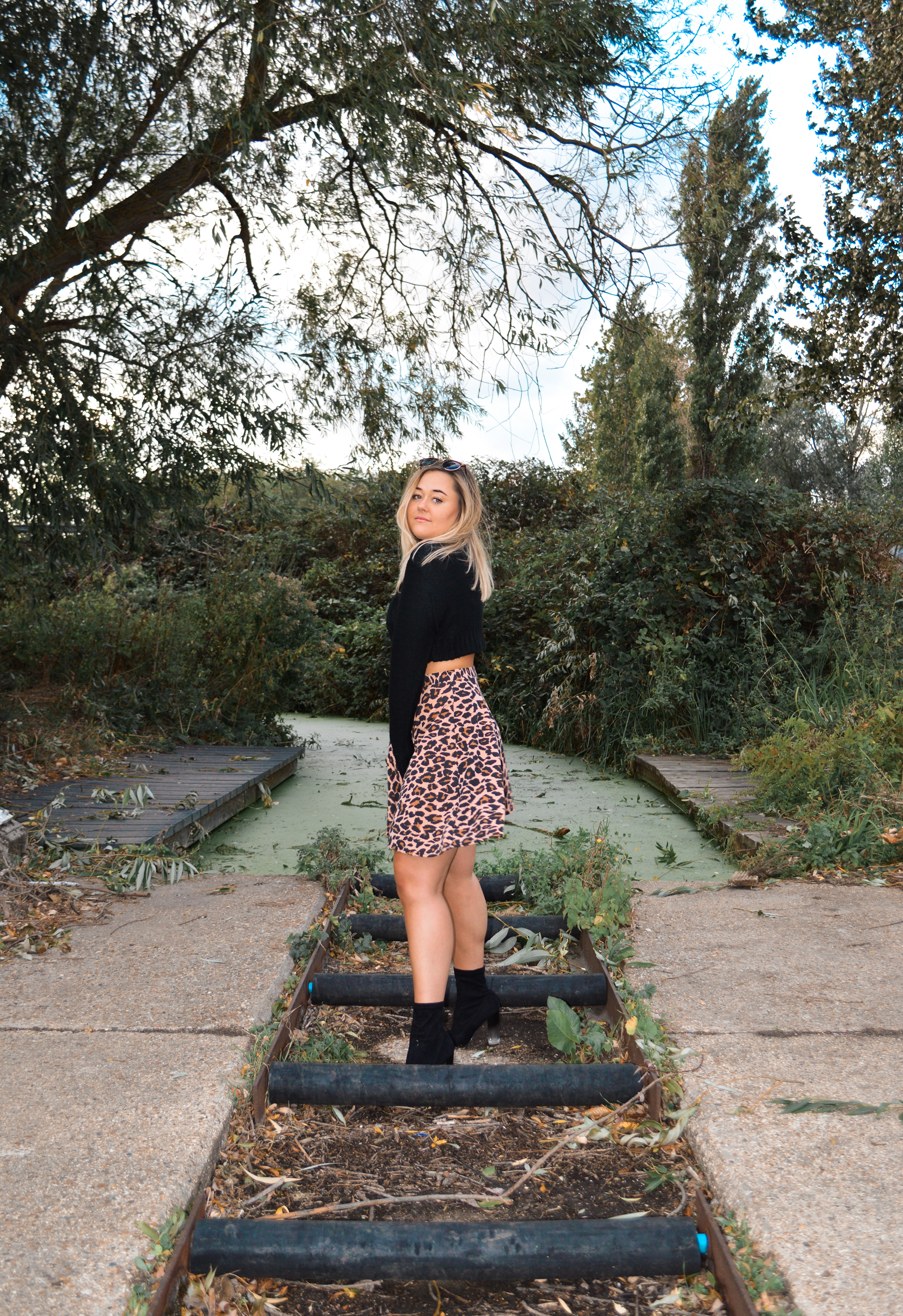 Hannah wears a black turtleneck, leopard print skater skirt and black sock boots with a perspex heel