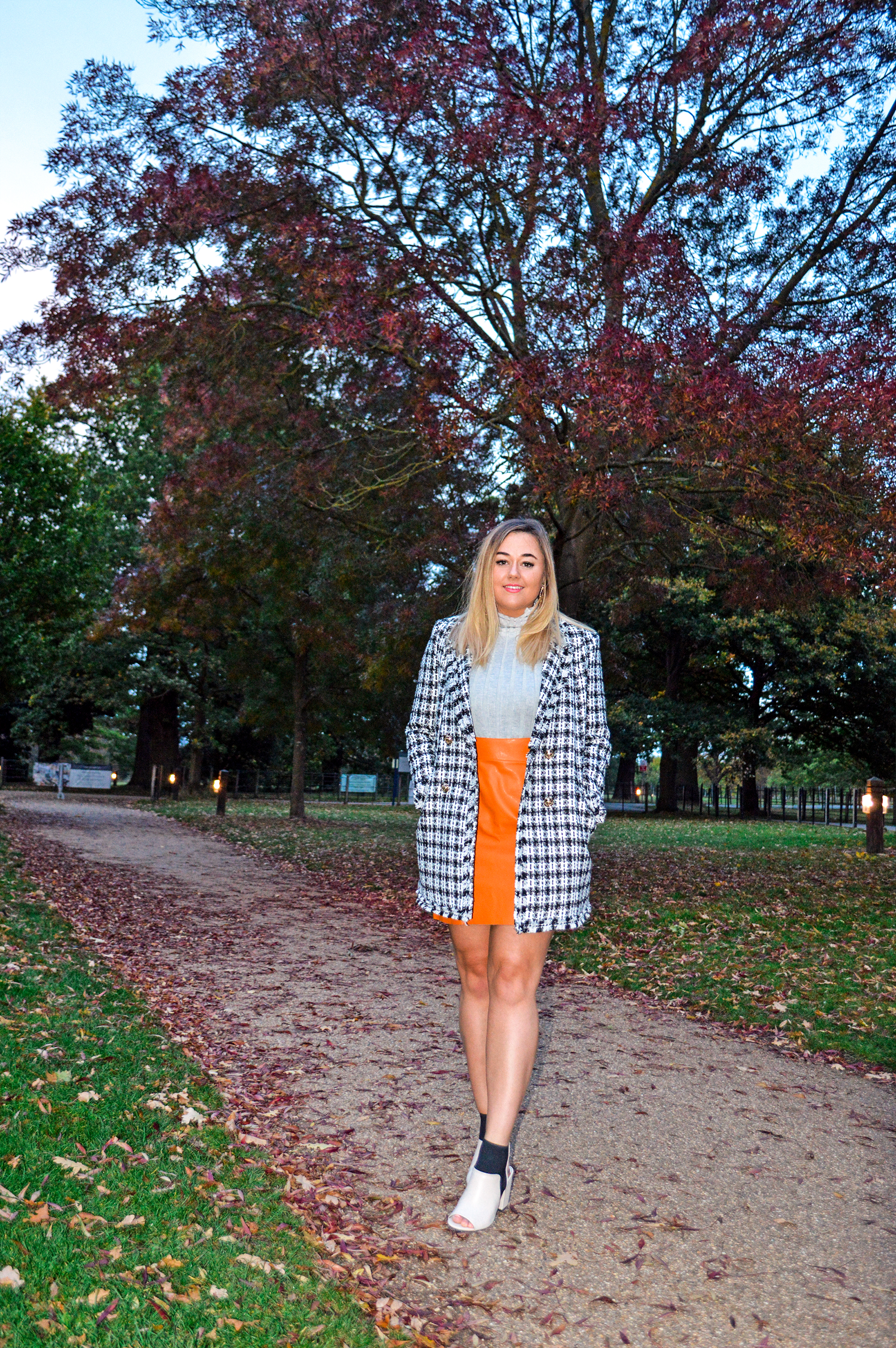 Hannah stands on a pavement surrounded by orange and red leaves and trees. Wearing sleeveless turtleneck grey sweater, faux leather orange skirt, ankle boots and bouclé jacket.