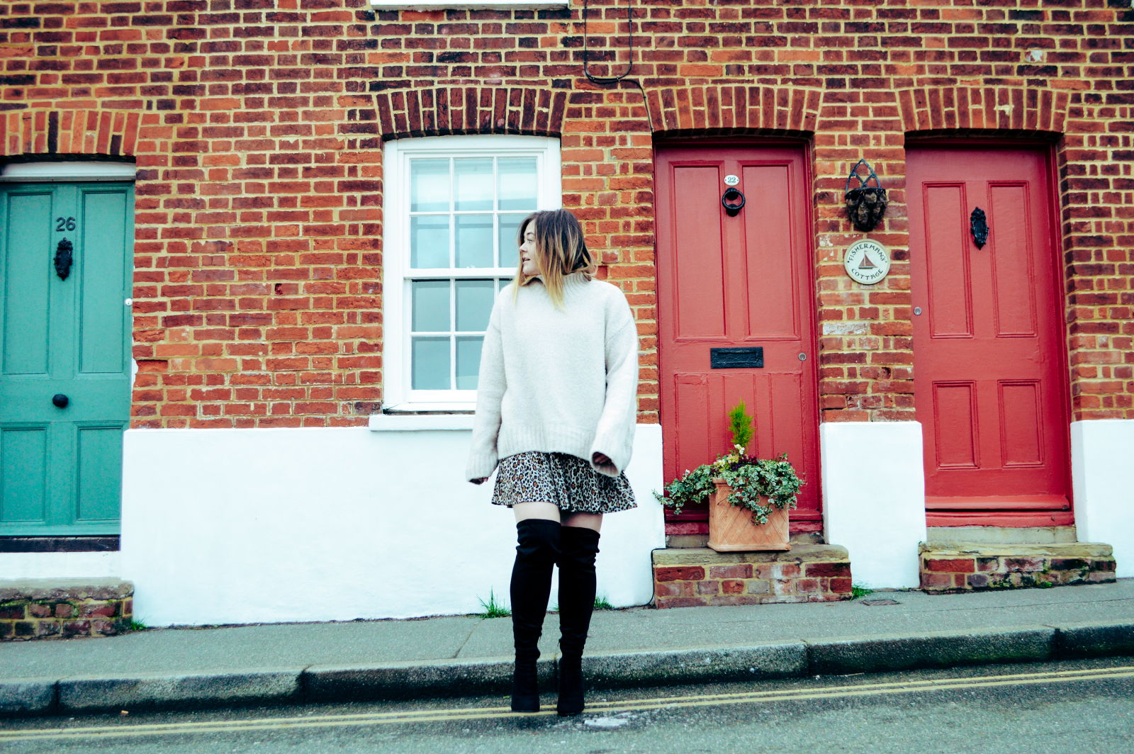 Hannah steps off of the pavement looking to the left, in front of a blue door and two red doors. Wearing a Zara leopard dress and a cream oversized jumper with over the knee black boots.