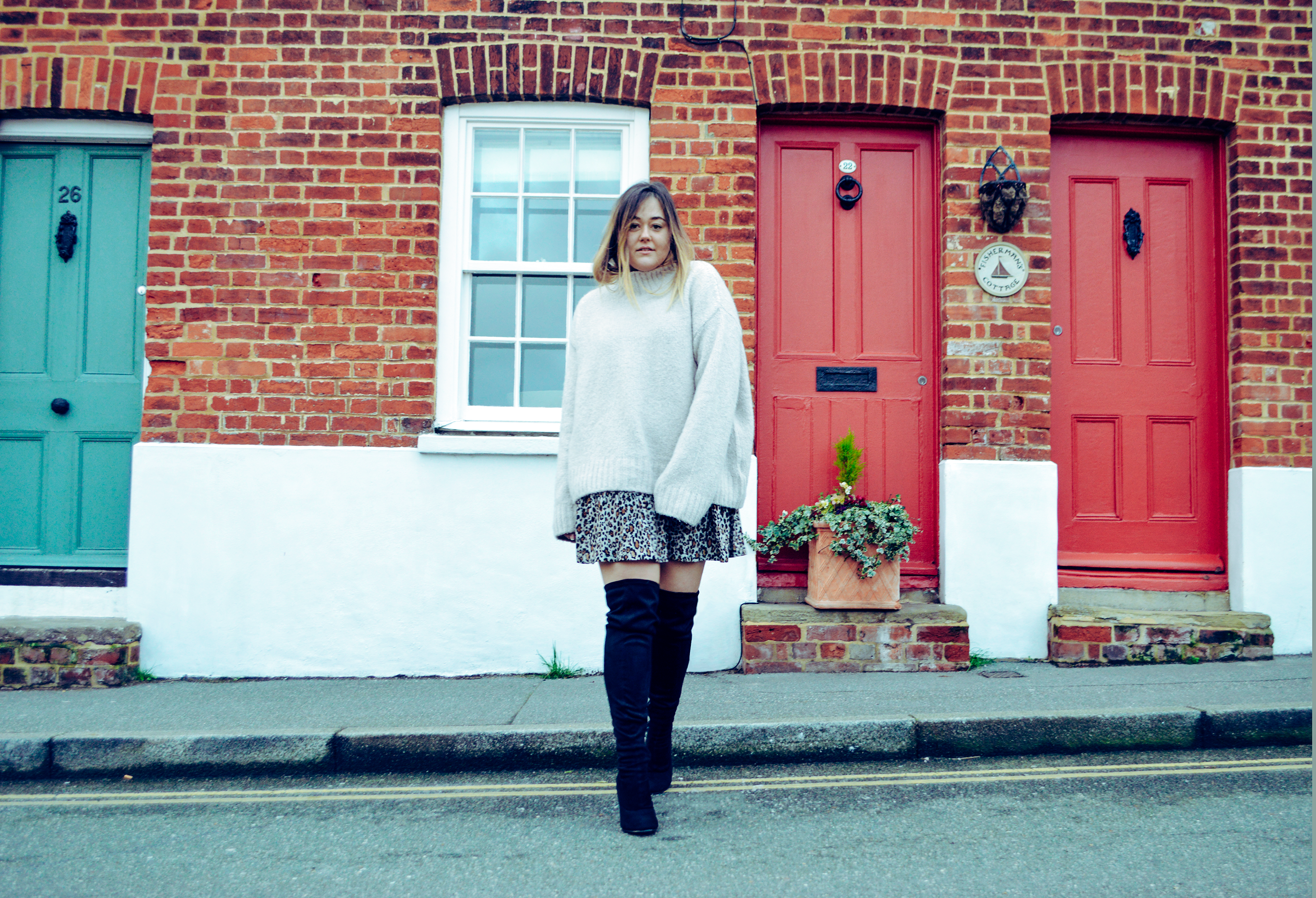 Hannah steps off of the pavement looking forward, in front of a blue door and two red doors. Wearing a Zara leopard dress and a cream oversized jumper with over the knee black boots.
