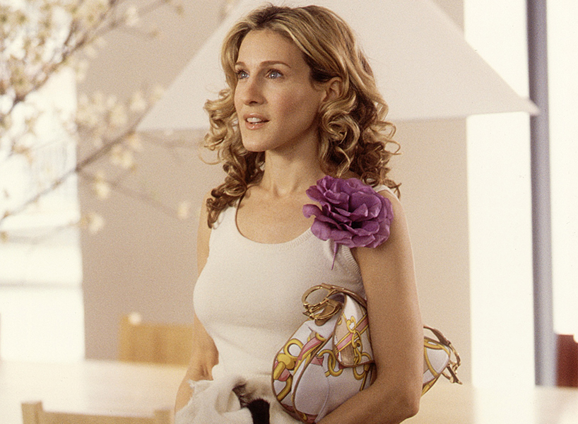 Carrie Bradshaw played by Sarah Jessica Parker in an episode of 2000's Sex and the City. She wears a Dior saddle bag (original) with a white vest top and a purple flower brooch on the strap.