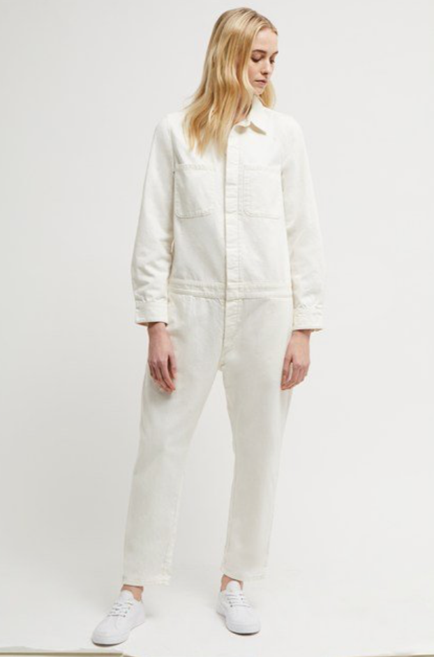 Blonde woman wearing a white boiler suit with trainers